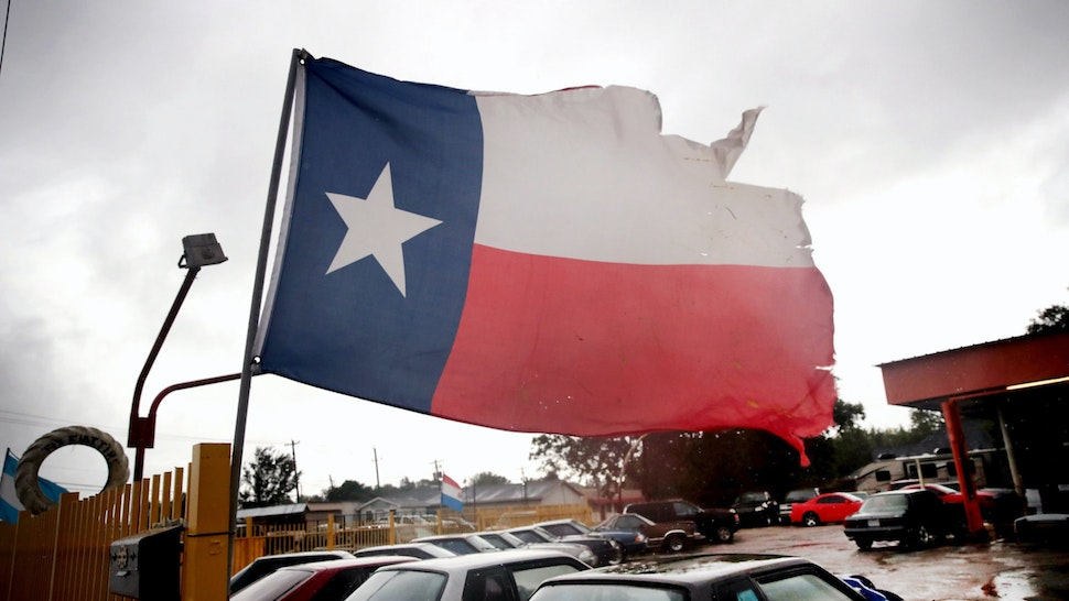 Wind from Hurricane Harvey batters a Texas flag on August 26, 2017 in Houston, Texas.