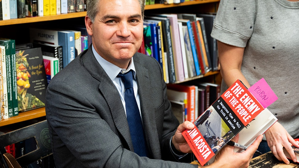 """WASHINGTON, D C , UNITED STATES - 2019/06/18: Jim Acosta holds his book """"The Enemy of the People: A Dangerous Time to Tell the Truth in America"""" at the Politics and Prose bookstore in Washington, DC."""