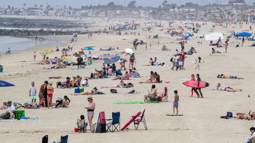 NEWPORT BEACH, CA -- TUESDAY, APRIL 28, 2020: Beach-goers enjoy a partially-sunny, warm day on the beach near the pier in Newport Beach, CA, on April 28, 2020. Newport Beach City Council members are holding a special meeting to discuss closing the city's beaches for the next few weekends following Gov. Gavin Newsom's criticism of the large crowds and lack of social distancing.