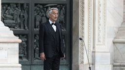TOPSHOT - Italian tenor and opera singer Andrea Bocelli sings during a rehearsal on a deserted Piazza del Duomo in central Milan on April 12, 2020, prior to an evening performance without public for the world wounded by the pandemic, during the country's lockdown aimed at curbing the spread of the COVID-19 infection, caused by the novel coronavirus.