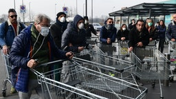 Residents wait to be given access to shop in a supermarket in small groups of forty people on February 23, 2020 in the small Italian town of Casalpusterlengo, under the shadow of a new coronavirus outbreak, as Italy took drastic containment steps as worldwide fears over the epidemic spiralled.