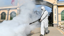 A volunteer sprays disinfectant at a school as the school prepares for students returning after the term opening was delayed due to the COVID-19 coronavirus outbreak, in Shangqiu in China's central Henan province on April 3, 2020.