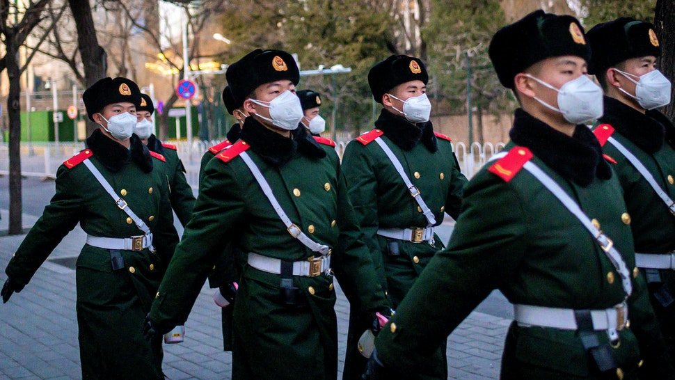 This picture taken on March 1, 2020 shows paramilitary police officers wearing face masks as they walk along a street in Beijing. - The global death toll from the new COVID-19 coronavirus epidemic surpassed 3,000 on March 2 after dozens more died at its epicentre in China and cases soared around the world, with a second fatality on US soil.