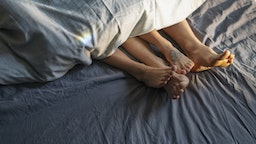 Couple's feet sticking out from under duvet in bed