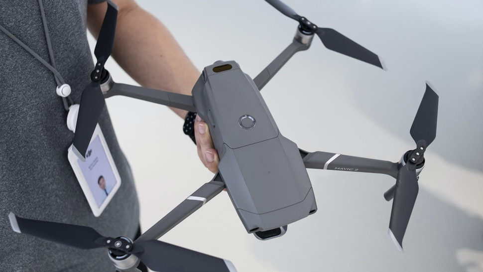 CAUSEWAY BAY, HONG KONG, HONG KONG ISLAND, CHINA - 2018/08/24: An employee from Chinese Technology company DJI holds the new DJI Mavic 2 Pro drone a day after it was officially announced its release at its flagship store in Hong Kong. Drone manufacturing leader DJI releases 2 of it's latest products, the Marvic 2 pro and the Marvic 2 zoom on 23rd August 2018. The Marvic 2 Pro is equipped with a upgraded 1 inch camera sensor for improved quality, while the Marvic 2 zoom allows users to use the digital zoom function in flight.