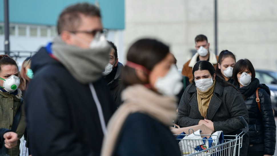 Residents wearing respiratory mask wait to be given access to shop in a supermarket in small groups of forty people on February 23, 2020 in the small Italian town of Casalpusterlengo, under the shadow of a new coronavirus outbreak, as Italy took drastic containment steps as worldwide fears over the epidemic spiralled.