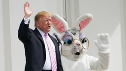 TOPSHOT - US President Donald Trump and the Easter Bunny wave during the annual White House Easter Egg Roll on the South Lawn of the White House in Washington, DC on April 22, 2019.