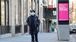 An NYPD police officer is seen wearing a protective face mask next to a LinkNYC screen with information related to COVID-19 as the coronavirus continues to spread across the United States on March 27, 2020 in New York City.
