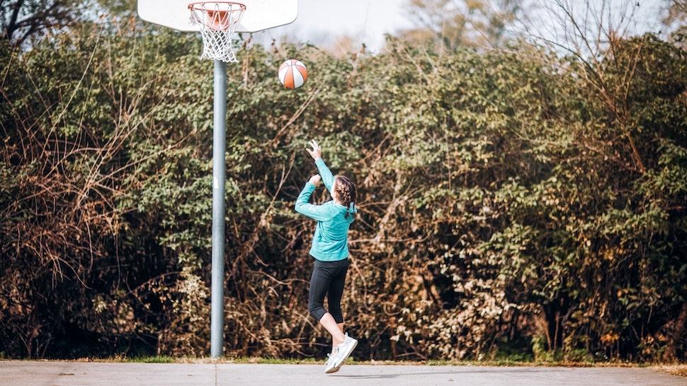 pre-teen girl shooting a layup on outdoor basketball court - stock photo
