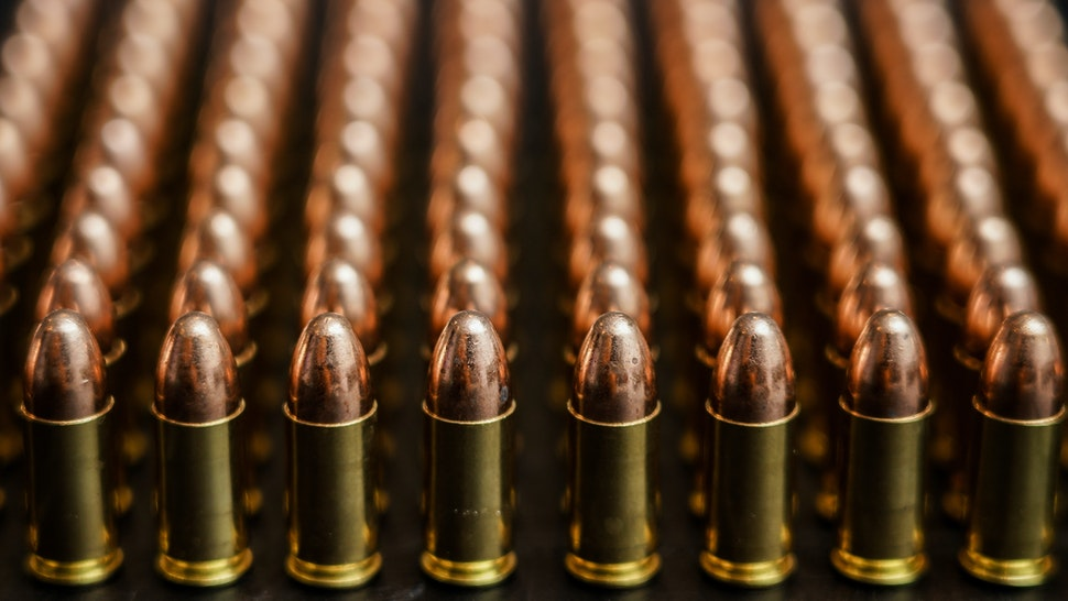 Many bullets or ammunition standing in straight line with blurred background. 9mm