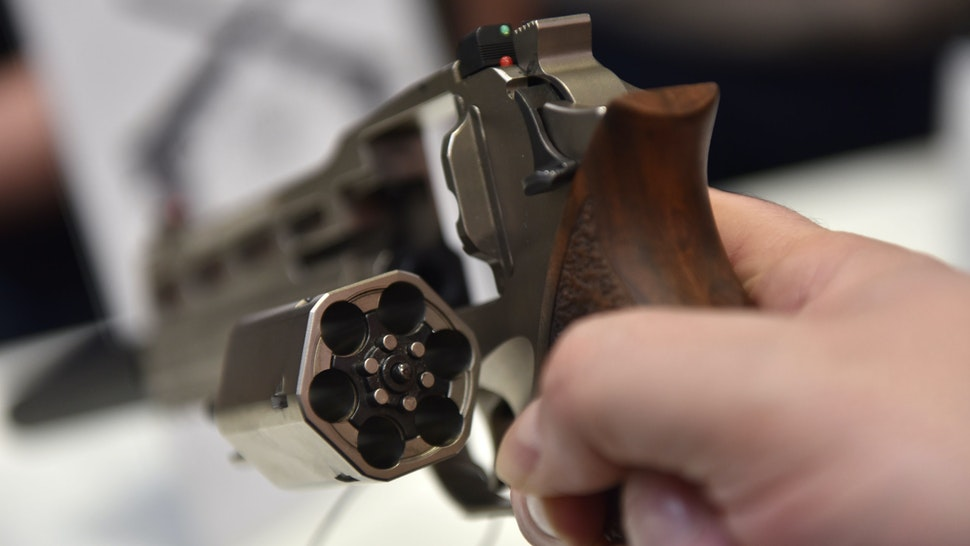 BIRMINGHAM, ENGLAND - FEBRUARY 15: A visitor holds a Wilson revolver pistol hand gun at the Great British Shooting Show at NEC Arena on February 15, 2019 in Birmingham, England. The show is the UK's flagship shooting event, the shooting industry's leading manufacturers, distributors, retailers and shooting organisations come together to offer visitors the largest and most varied choice of shooting related products. (Photo by John Keeble/Getty Images)
