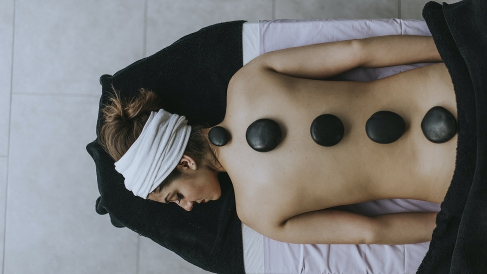 Young woman with heated stones on her back - stock photo