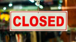 """A glass door with red and white """"closed"""" store sign"""