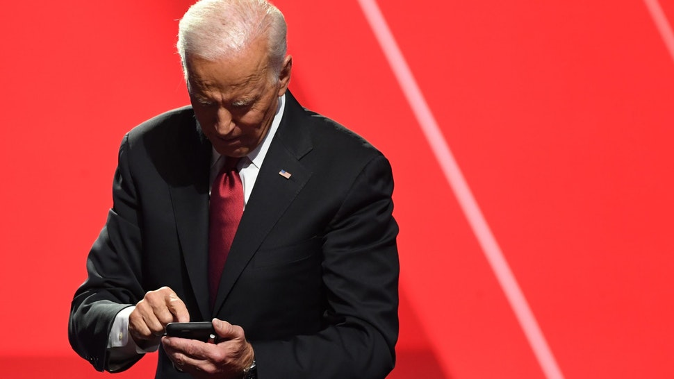Democratic presidential hopeful former US Vice President Joe Biden looks at his phone after the fourth Democratic primary debate of the 2020 presidential campaign season co-hosted by The New York Times and CNN at Otterbein University in Westerville, Ohio on October 15, 2019. (Photo by SAUL LOEB / AFP) (Photo by SAUL LOEB/AFP via Getty Images)