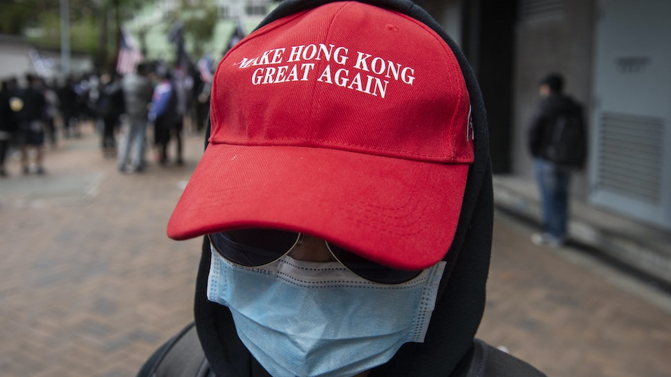 """HONG KONG, CHINA - FEBRUARY 19, 2020: A protester wearing a """"Make Hong Kong Great Again"""" hat takes part in a protest against the use of a quarantine center in Cheung Sha Wan in Hong Kong.- PHOTOGRAPH BY Miguel Candela / Echoes Wire/ Barcroft Media (Photo credit should read Miguel Candela / Echoes Wire/Barcroft Media via Getty Images)"""