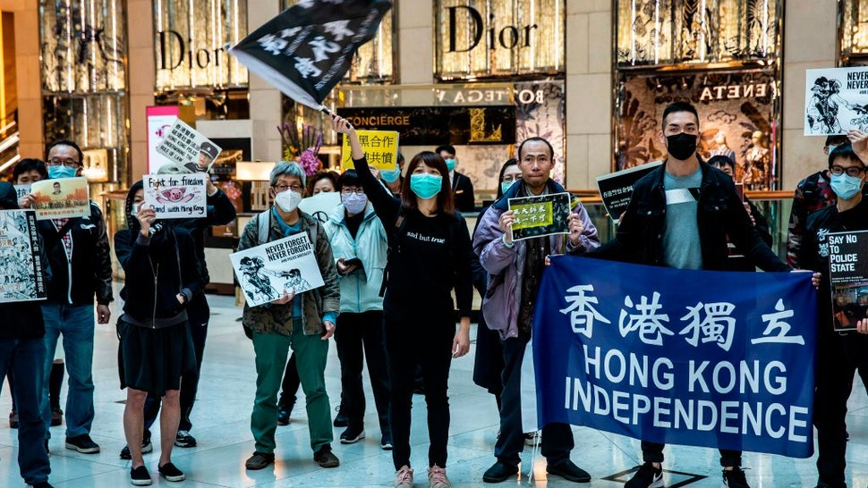 Office workers and protesters gather during a pro-democracy demonstration in a mall in the central district of Hong Kong on February 21, 2020.