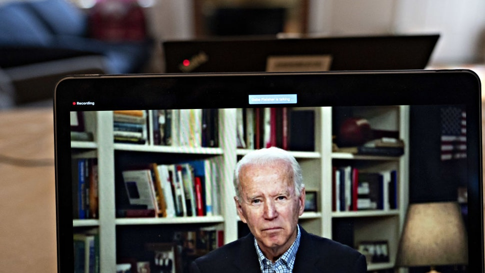 Former Vice President Joe Biden, 2020 Democratic presidential candidate, listens to a question during a virtual press briefing on a laptop computer in this arranged photograph in Arlington, Virginia, U.S., on Wednesday, March 25, 2020.