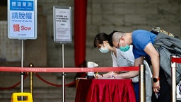 A masked couple fill in forms with personal information, amid concerns of the COVID-19 coronavirus, while visiting the Chiang Kai-shek (CKS) Memorial Hall in Taipei on March 31, 2020