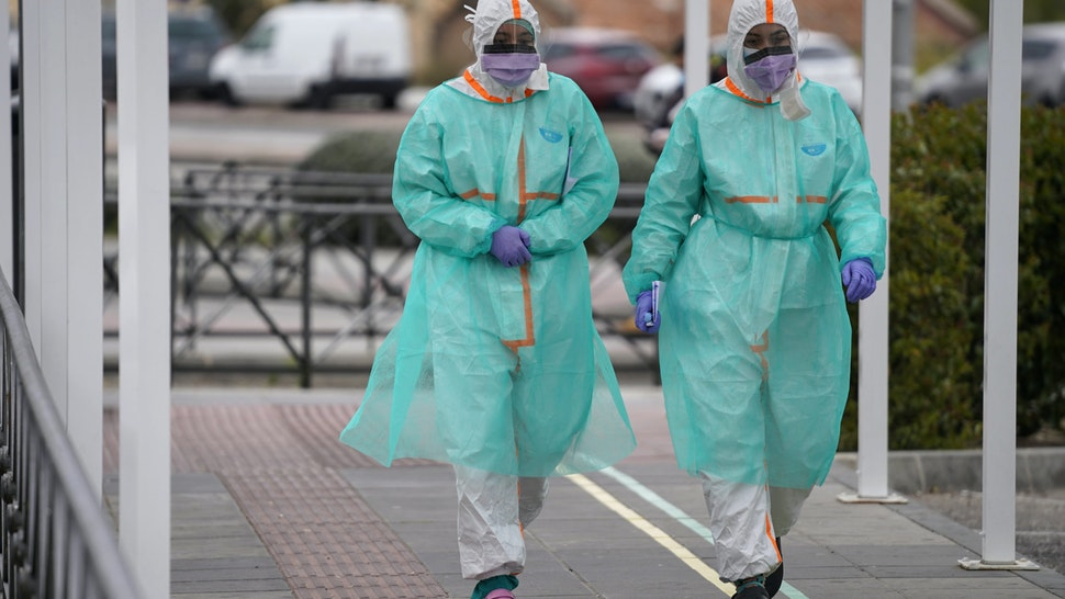 Medical workers wearing protective face masks and full body outfits walk outside the emergency department of the 12 de Octubre hospital in Madrid, Spain, on Monday, March 30, 2020. Spain suffered its deadliest day yet of the coronavirus outbreak this weekend as Prime Minister Pedro Sanchez convened an emergency cabinet meeting to try to chart a way out of the crisis rapidly engulfing the nation. Photographer: Paul Hanna/Bloomberg via Getty Images