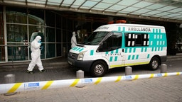 Healthcare workers wearing protective suits enter an ambulance in front of the Hotel Melia Barcelona Sarria on April 2, 2020 in Barcelona, as the hotel was transformed into a medical structure to treat the least serious cases amid the outbreak caused by the novel coronavirus.