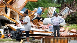 Sylvia Salley, right, and Evelyn Wise looks over what remains of a storm damaged home April 13, 2020 in Livingston, South Carolina. A string of storms caused more than a dozen deaths across the southern United States.