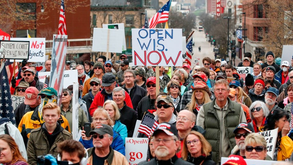 People hold signs during a protest against the coronavirus shutdown in front of State Capitol in Madison, Wisconsin, on April 24, 2020.