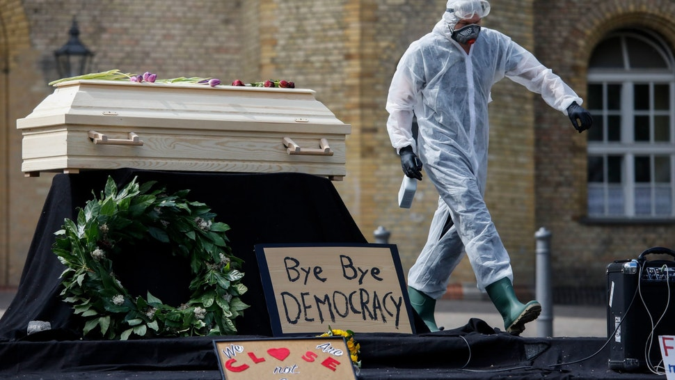 "A man wears protective gear and sprays disinfectant as a small group of people stage a so-called ""Funeral for Democracy"" to protest the government's measures of social distancing, in front of the Kuenstlerhaus (Artist's House) Bethanien in Berlin's Kreuzberg district on April 25, 2020, amid novel coronavirus COVID-19 pandemic. (Photo by David GANNON / AFP) (Photo by DAVID GANNON/AFP via Getty Images)"