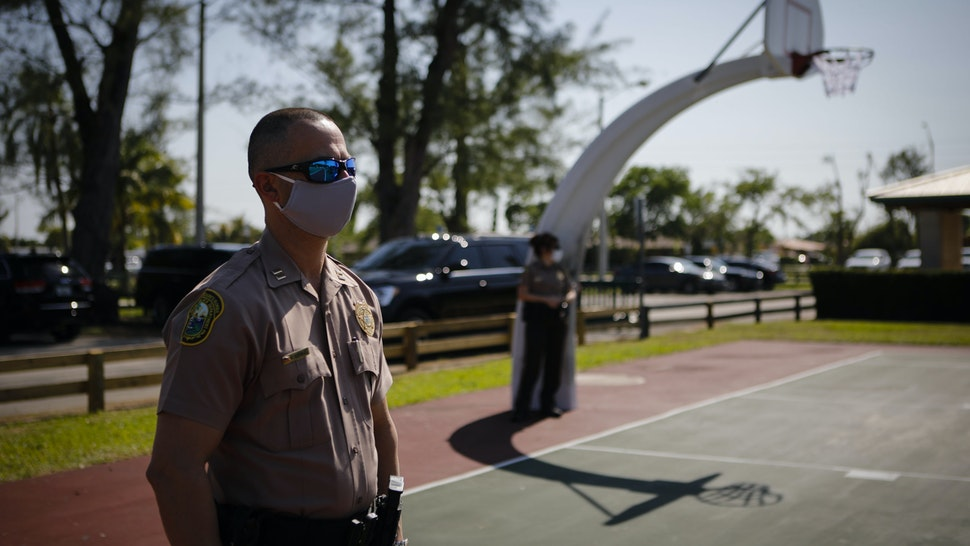 A police officer wears a protective mask while listening to Carlos Gimenez, mayor of Miami-Dade County, not pictured, speak during a news conference in Miami, Florida, U.S., on Monday, April 27, 2020. On Wednesday Miami-Dade's six-week closure order for parks will officially end, replaced by a new set of rules aimed at limiting close encounters during the coronavirus pandemic, according to the Miami Herald. Photographer: Eva Marie Uzcategui/Bloomberg via Getty Images