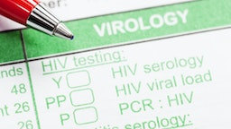 Red pen on virology form ordering HIV tests - stock photo
