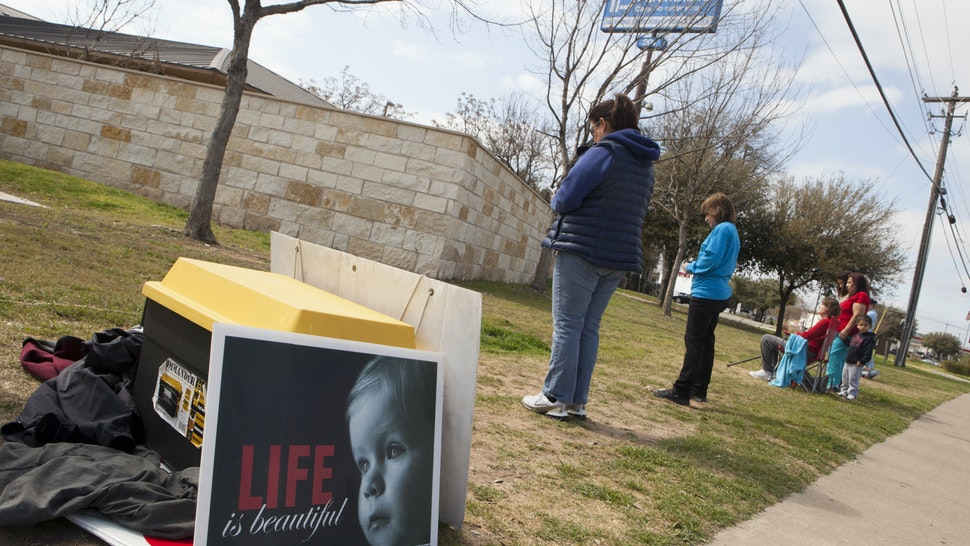AUSTIN, TEXAS - FEBRUARY 22: Anti-abortion, pro-life activists pray outside a Planned Parenthood clinic that offers abortions, on February 22, 2016 in Austin, Texas. They sign up to pray at the vigil for one hour each in support of a campaign called 'Forty Days for Life.' At least two people will be at the vigil for forty days during daylight hours. After the passage of a restrictive abortion bill in the Texas legislature, HB2, both sides of the abortion debate are active in getting their positions known. The US Supreme Court will rule on whether to overturn the bill. (Photo by Melanie Stetson Freeman/The Christian Science Monitor via Getty Images)