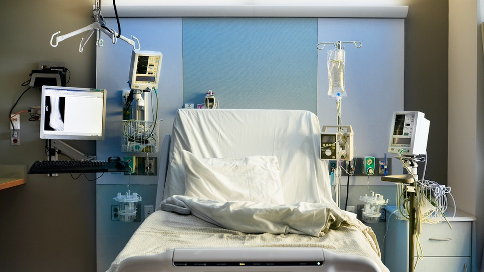 Straight-on view of empty hospital bed with medical equipment.