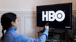 PARIS, FRANCE - NOVEMBER 21: In this photo illustration, the HBO logo is displayed on a television screen on November 21, 2019 in Paris, France. HBO is an American pay TV channel that produces and broadcasts TV shows.