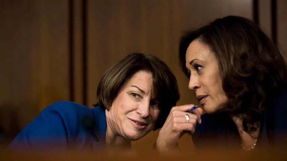 WASHINGTON, DC - Senators Amy Klobuchar (D-MN) and Kamala Harris (D-CA) speak quietly during the Supreme Court nominee Brett Kavanaugh's confirmation hearing in the Senate Judiciary Committee on Capitol Hill in Washington, DC on Wednesday September 5, 2018.