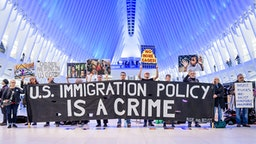 "MANHATTAN, NEW YORK, UNITED STATES - 2020/01/06: Protesters holding a banner at the silent protest. Members of the activist group Rise And Resist gathered a silent protest inside The Oculus at the World Trade Center, holding protest signs, a banner reading ""U.S. Immigration Policy Is A Crime"", photographs of the children who have died in ICE custody, and photographs of the detention camps to object to Border Patrol and ICE treatment of immigrants, refugees, and asylum seekers, calling on the Trump administration to immediately process all asylum seekers."
