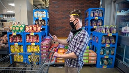 WASHINGTON,DC-APR6: Matt Gillette, a 36 year-old Instacart shopper, prepares to fulfill an order at a Giant supermarket in Washington, DC, April 6, 2020. For the past two years he's been part of the gig economy, driving for Lyft, doing handiwork on TaskRabbit. The work was so unstable he's been on the verge of homelessness, crashing with some friends and asking others to take in his beloved dog, a lab mix named Nitro. For years there has been talk of a divided America, of an economy that's highly beneficial to some and detrimental to others. The wrath of a highly contagious, sometimes lethal virus has shown us where, precisely, it stands: at the front door. On one side are people who have the luxury of staying safely at home, working -- or not -- and ordering whatever they want to be delivered. On the other side are those doing the delivering.