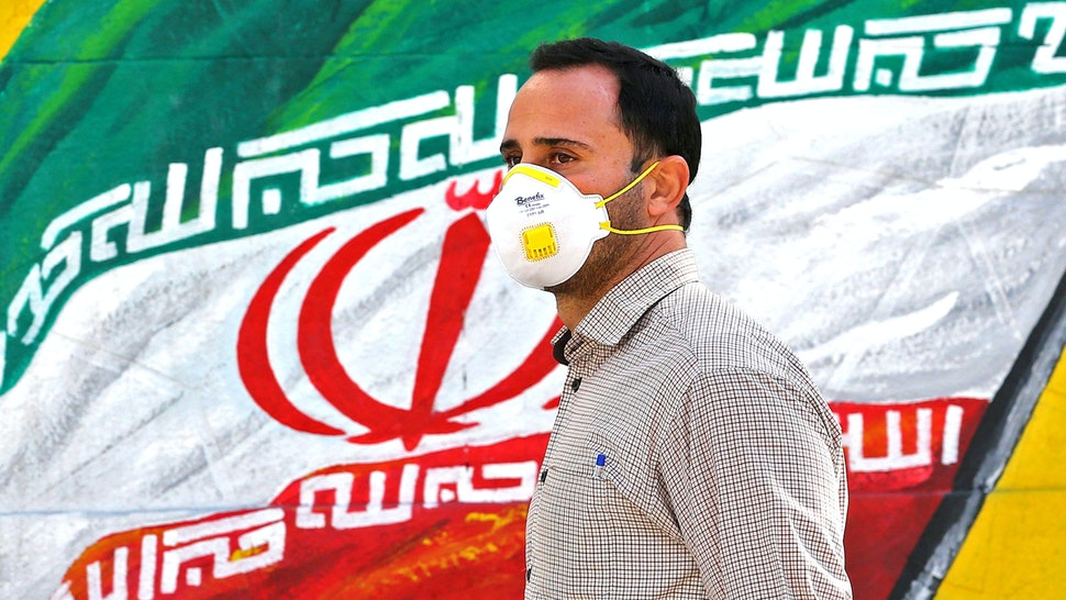 An Iranian man wearing a mask walks past a mural displaying his national flag in Tehran on March 4, 2020. - Iran has scrambled to halt the rapid spread of the COVID-19 virus, shutting schools and universities, suspending major cultural and sporting events, and cutting back on work hours.