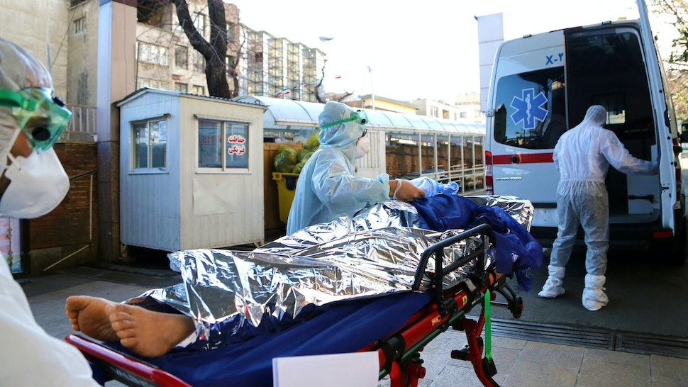 TEHRAN, IRAN - MARCH 02: Ambulance staff wearing protective masks and suits take a patient to a hospital as death toll from coronavirus (Covid-19) rises to 66 in Tehran, Iran on March 02, 2020. The death toll from coronavirus in Iran has reached to 66 as 12 more people lost their lives due to the virus and the total number of confirmed cases rose to 1,501.