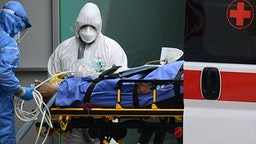 Medical workers stretch a patient from an Italian Red Cross ambulance into an intensive care unit set up in a sports center outside the San Raffaele hospital in Milan, on March 23, 2020 during the COVID-19 new coronavirus pandemic.