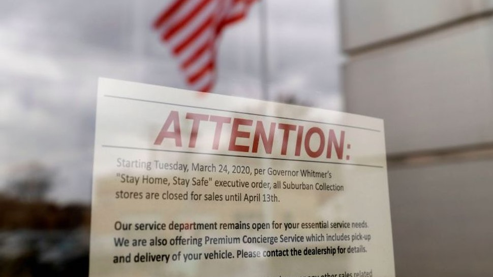 A closed sign is seen on the Suburban Buick GMC that is currently closed by Michigan Governor Gretchen Whitmer to stop the spread of coronavirus,COVID-19, in Ferndale, Michigan on March 26, 2020. - President Donald Trump, keen for an early lifting of economically costly social distancing measures against the coronavirus, said he would propose dividing the United States by risk levels. In a letter to state governors released by the White House, Trump said that better testing now allows the mapping of virus threat on a local level. (Photo by JEFF KOWALSKY / AFP)