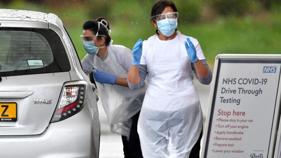 A medical worker tests a key worker for the novel coronavirus COVID-19 at a drive-in testing facility at the Chessington World of Adventures Resort in Greater London on April 28, 2020. - Britain's health ministry on April 27 said the total toll of those having died after testing positive for COVID-19 in hospital had risen to 21,092. (Photo by Ben STANSALL / AFP)