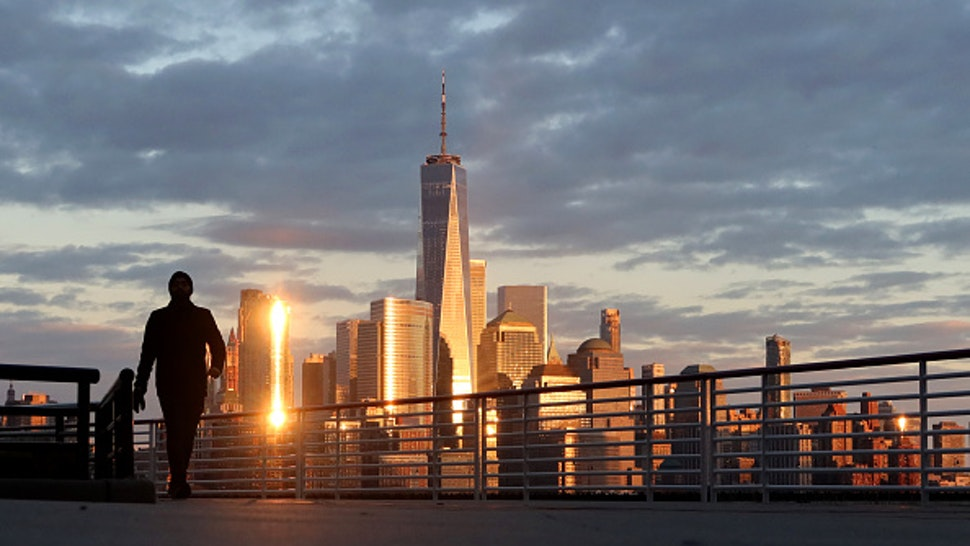 JERSEY CITY, NJ - APRIL 4: The sun sets on the skyline of lower Manhattan and One World Trade Center in New York City on April 4, 2020 as seen from Jersey City, New Jersey.