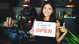 Portrait Of Smiling Young Woman Holding Open Sign While Standing In Cafe - stock photo