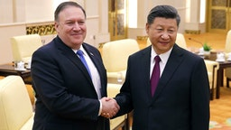 US Secretary of State Mike Pompeo (L) shakes hands with Chinese President Xi Jinping as they pose for photograph at the Great Hall of the People in Beijing on June 14, 2018.