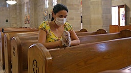 Parishioner Laura Sanchez holds a rosary while she prays wearing mask and protective gloves at Saint Jude Melkite Greek Catholic Church on Easter Sunday as the novel coronavirus pandemic continues on Sunday, April 12, 2020 in Miami.