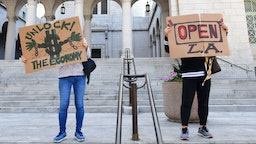 """Protestors display placards on the steps of City Hall, demanding the """"Stay at Home"""" order to be lifted and the government to re-open the state during an """"Open California"""" rally in downtown Los Angeles, on April 22, 2020. - Over the past week there have been scattered protests in several US states against confinement measures, from New Hampshire, Maryland and Pennsylvania to Texas and California. (Photo by Frederic J. BROWN / AFP) (Photo by FREDERIC J. BROWN/AFP via Getty Images)"""