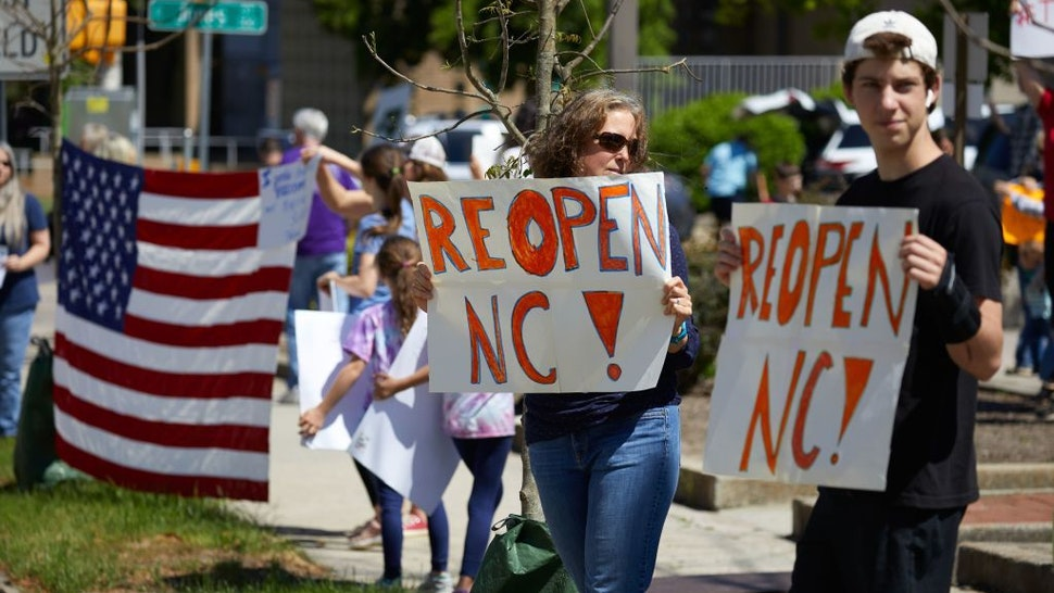 Protesters from a grassroots organization called REOPEN NC demonstrate against the North Carolina coronavirus lockdown at a parking lot adjacent to the North Carolina State Legislature in Raleigh, North Carolina, on April 14, 2020. - The group was demanding the state economy be opened up no later than April 29. (Photo by Logan Cyrus / AFP)
