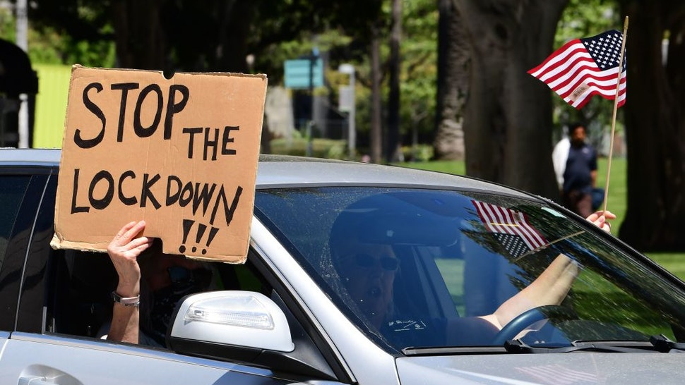 "Protesters display placards and flags from their vehicle demanding the ""Stay at Home"" order to be lifted and the government to re-open the state during an ""Open California"" rally in downtown Los Angeles, on April 22, 2020. - Over the past week there have been scattered protests in several US states against confinement measures, from New Hampshire, Maryland and Pennsylvania to Texas and California. (Photo by Frederic J. BROWN / AFP) (Photo by FREDERIC J. BROWN/AFP via Getty Images)"