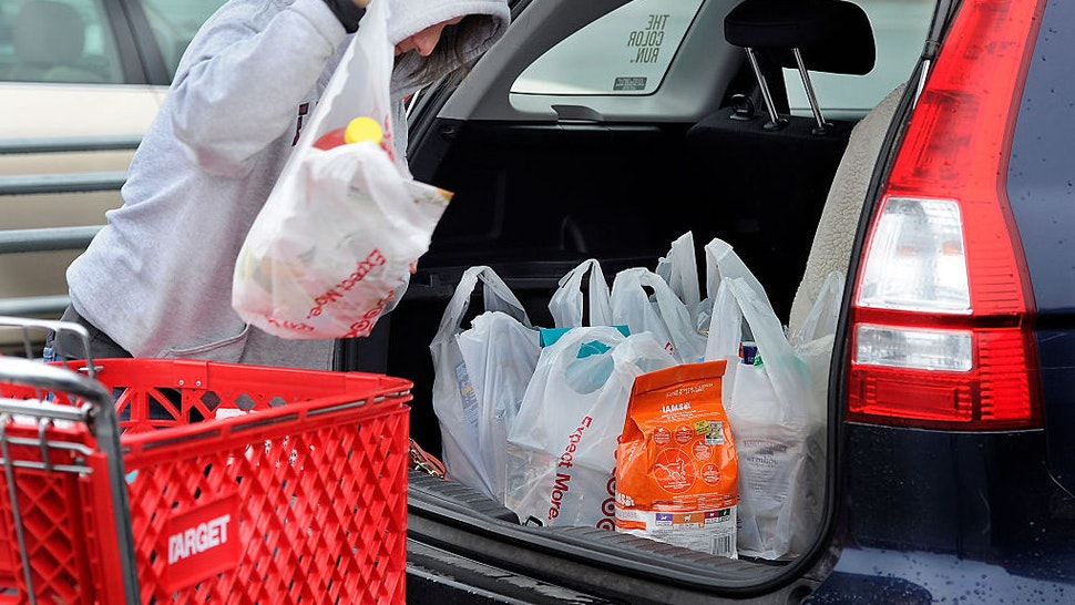 """Melody Bertrand of Durham fills her car with products from Target in plastic bags. She said she is a dedicated recycler but forgot to bring her reusable bags to Target. """"I always recycle the plastic bags by bringing them back and putting them into the plastic bag recycled container inside Target,"""" she said. """"They should let people take the merchandise to their cars and put the bags back into the cart to be recycled by the store. The store should make the bags bigger and put more into them, she added."""" (Photo by Gordon Chibroski/Staff Photographer)"""