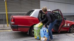 A woman loads newly purchased toilet paper and tissues into a taxi in Hong Kong, China, on Thursday, Feb. 6, 2020. Hong Kong has been struggling with a shortage of face masks to protect against the coronavirus outbreak. Now it could be facing a run on toilet paper.
