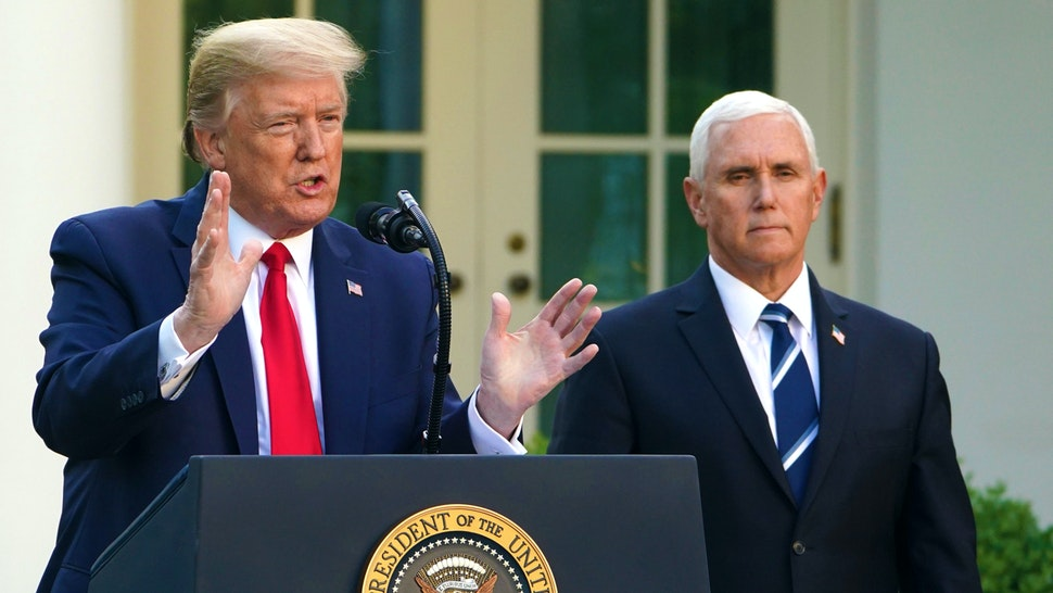 US President Donald Trump speaks as US Vice President Mike Pence look on during a news conference on the novel coronavirus, COVID-19, in the Rose Garden of the White House in Washington, DC on April 27, 2020.